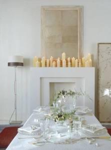 Mesa decorada en blanco y cristal con chimenea llena de velas. Decoración realizada por la revista Nuevo Estilo