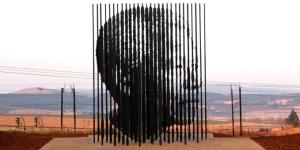 Monumento conmemorativo de los 50 años del arresto de Mandela por el artista suráfricano Marco Cianfanelli .La obra está compuesta por 50 columnas de acero, una por cada año que pasó privado de libertad, de entre 6,5 y 9 metros de altura. La figura se erige en Kwazulu, ciudad donde se cometió el arresto. Agosto 2012.